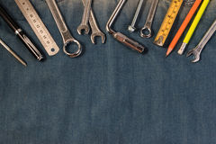 Strappi gli strumenti sui lavoratori di un denim con spazio per testo Giorno di lavoro felice Immagine Stock