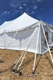 Straps hold up a white tent in a field Stock Images
