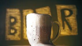 Straripamenti della schiuma della birra sopra il bordo della tazza Lotti di schiuma in una tazza di birra Birra leggera fredda co archivi video