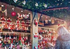 Strasbourg, Alsace, France. Christmas market. STRASBOURG, FRANCE - DECEMBER 24, 2015. A woman choosing christmas decoration at market Stock Image