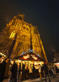 Strasbourg cathedral and Christmas Market. STRASBOURG, FRANCE - NOVEMBER 29, 2014: Full lenght Strasbourg Cathedral with People walking among Christmas stands Stock Image