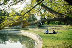 Male friend near lake resting. STRASBOURG, FRANCE - APR 7, 2017: French male friends resting on grass enjoying the sun on an early spring day in Strasbourg stock images