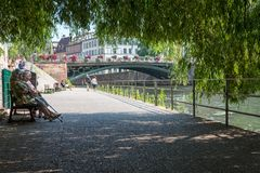 Strasbourg, France - August 11, 2015 : Elderly people sitting on a bench, resting in the shade, on summer Royalty Free Stock Photos