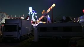 Night scene tilt-shift at dusk amusement park. Strasbourg, France - Circa 2018: Cinematic night scene of amusement park with parked white trucks and Ferris wheel stock video footage