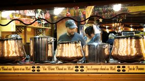 Man preparing mulled wine Christmas Chalet. Strasbourg, France - circa 2018: Owner arranging the Christmas market stalls with mulled wines recipients a day stock video footage