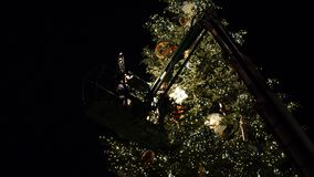 Workers on top of Christmas tree decorating in French Christmas capital. Strasbourg, France - circa 2018: people on top of telescopic crane in central Place stock video
