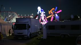 Night scene tilt-shift at dusk amusement park. Strasbourg, France - Circa 2018: Workers smoking near white Renault Trailer truck - night scene of amusement park stock footage