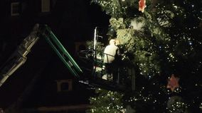 Workers preparing the Christmas tree in central square. Strasbourg, France - circa 2018: Workers on top of telescopic crane in central Place Kleber preparing stock video
