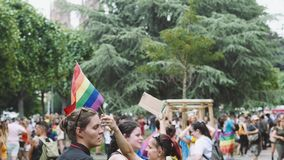 Annual gay pride parade with girl giving free hugs. STRASBOURG, FRANCE - CIRCA 2018: Young girl giving free hugs waving gay flag and jumping at annual FestiGays stock video footage