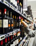 Woman buying shopping for wine in supermarket France stock images