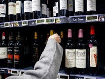Woman buying shopping for wine in supermarket France stock photography