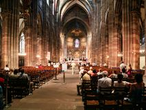 Church service in Strasbourg Cathedra. STRASBOURG, FRANCE - JULY 10, 2010: people during church service in Strasbourg Cathedral . Roman Catholic cathedral was Royalty Free Stock Images