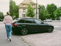 Casual French woman walking past a black luxury BMW wagon stock photo