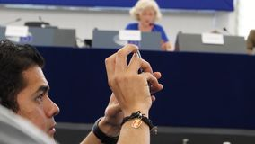 European Parliament in Strasbourg open days with people. Strasbourg, France - May 14, 2017: Young man taking photos from EP seat during official open days stock video