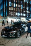 Shopper passing by luxury black Renault Talisman. STRASBOURG, FRANCE - NOV 21, 2017: Shopper passing by luxury black Renault Talisman reflecting red Christmas Stock Image