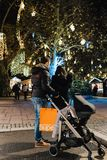 Young couple with pram stroller admiring the Christmas illuminat. STRASBOURG, FRANCE - NOV 29, 2017: Young couple with pram stroller admiring the Christmas Royalty Free Stock Photo