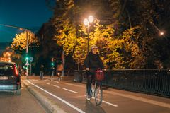 Senior woman riding a bike at night in central Strasbourg stock images