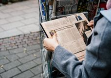 Woman buying FT Weekend newspaper. STRASBOURG, FRANCE - OCT 28, 2017: Woman buying FT Weekend newspaper at press kiosk featuring US economy after hurricanes Royalty Free Stock Images