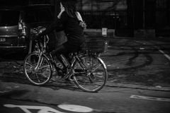 Woman on bicycle at night in city commuting home Stock Photography