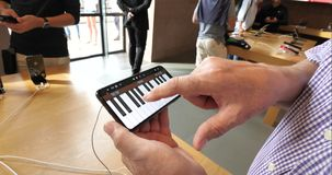 Playing Piano on iPhone XS Max. STRASBOURG, FRANCE - SEP 21, 2018: handheld video of senior man using GarageBand playing piano POV music creation app on the new stock footage