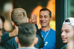 Apple Genius man wearing blue t-shirt welcoming customers Stock Photos