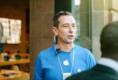 Apple Genius man wearing blue t-shirt welcoming customers Stock Images
