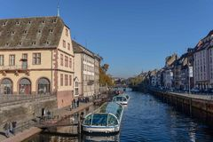 Strasbourg, water canal in Petite France area. timbered houses and trees in Grand Ile. Alsace, France. in the foreground water bus Royalty Free Stock Photography