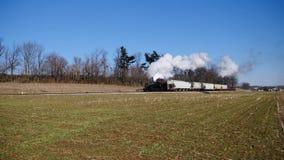 Strasburg, Pennsylvania, febrero de 2019 - cocer el tren combinado de la carga al vapor y del pasajero en Sunny Winter Day almacen de video
