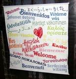 STRASBURGO, FRANCIA - 12 MARZO 2006 Segno inviato davanti ad una chiesa che accoglie favorevolmente gli ospiti in varie lingue ne Fotografie Stock Libere da Diritti
