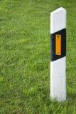 Strassenpfosten. Streetmark with reflector on the green grass Royalty Free Stock Photography