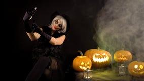 Straszna piękna dziewczyny czarownica świętuje Halloween, robi selfie z śmiesznymi rozjarzonymi płonącymi baniami w dymu Kobieta  zbiory wideo