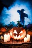 Straszna pomarańczowa bania na ciemnym polu i strach na wróble dla Halloween obraz royalty free