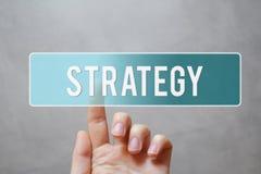 Stratégie - doigt appuyant sur le bouton transparent bleu photographie stock libre de droits
