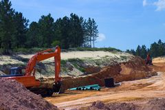 Strata of rock and dirt with heavy equipment. On road construction project Stock Photos