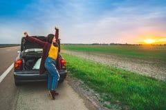 stratching在汽车长的汽车旅行附近的妇女 图库摄影