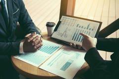 Strategia di analisi di due di affari colleghe di associazione e gesturing con la discussione del bilancio del grafico e della so fotografie stock libere da diritti
