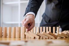 Strategia di legno del gioco, mano dell'uomo d'affari che ferma effetto di domino di legno di caduta rovesciato da continuo o dal immagine stock