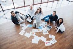 Strategia di pianificazione insieme Gruppo di affari che esamina le carte sul pavimento con il responsabile che indica un'idea co fotografie stock libere da diritti