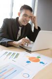 Strategic documents are focused. While Asian business man in background Stock Image