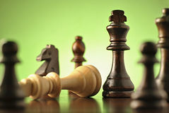 Strategic game of chess. With a view through various chess pieces to a dark wood king standing upright over a fallen lighter king Royalty Free Stock Images