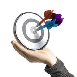 Strategic Marketing. One hand holding a target with three darts hitting the center, white background. Illustration of strategic marketing or business solutions Royalty Free Stock Image