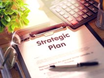 Strategic Plan - Text on Clipboard. 3D. Strategic Plan on Clipboard with Paper Sheet on Table with Office Supplies Around. 3d Rendering. Blurred and Toned Stock Photos