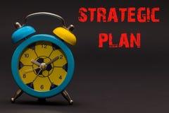 Strategic Plan written with alarm clock on black paper backgroun. D Stock Image
