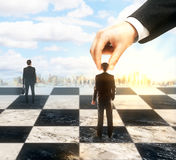 Strategic planning concept. Strategic planning and control concept with hand moving businesspeople on chessboard. City and sky background Royalty Free Stock Images