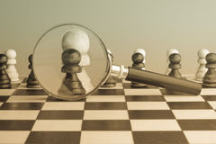 Strategic planning, intelligence concept photo with chess pawns and magnifier, retro sepia colors. Stock Photography