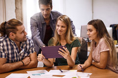 Strategic planning team in a meeting. Strategic planning team in a brain storming meeting with a lively discussion at a conference table with a tablet pc looking Stock Photo