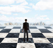 Strategic research concept. Strategic planning concept with businessman standing on chessboard and looking at city on sky background with clouds Royalty Free Stock Images