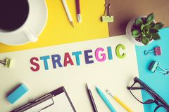 STRATEGIC word on desk office background with supplies. STRATEGIC  word on desk office background with supplies.Colorful of business working table.marketing Stock Images