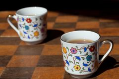 Strategie, die mit zwei Kaffeetassen auf Schachbrett denkt Morgenideenkonzept Stockbilder