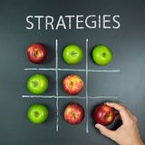 Strategies concept with tic tac toe game. Strategies concept with playing tic tac toe game using apples Stock Image